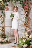 La jeune jeune mariée se tient sous la voûte des usines d'automne Images stock