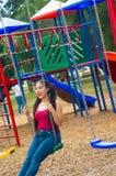 La jeune jolie adolescente avec le porc coupe la queue les jeans de port et le dessus pourpre, se reposant sur l'oscillation au t Image libre de droits