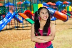 La jeune jolie adolescente avec le porc coupe la queue les jeans de port et le dessus pourpre, se tenant devant le terrain de jeu Photo libre de droits