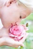 La jeune jolie femme apprécie l'odeur du rose s'est levée Image stock