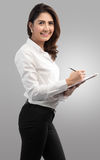 La jeune jolie femme d'affaires écrivent sur le presse-papiers Image stock
