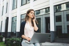 La jeune jolie femme d'affaires s'assied dans la rue urbaine et la discussion au sujet du travail sur l'information de smartphone photo stock