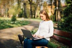 La jeune jolie femme d'affaires s'assied sur le banc dans la ville Photo stock