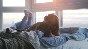 La jeune jolie femme dans des écouteurs détendant avec son beau grand chat de Maine Coon écoute la musique fixant dans le lit par clips vidéos