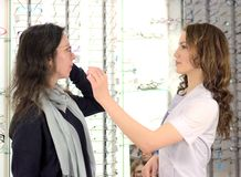 La jeune jolie femme essaye des verres d'oeil ? un magasin d'eyewear avec l'aide d'un employ? de magasin et des actions dans des  images libres de droits