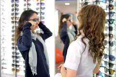 La jeune jolie femme essaye des verres de soleil ? un magasin d'eyewear avec l'aide d'un employ? de magasin image libre de droits
