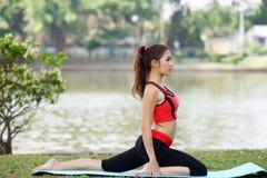 La jeune jolie femme faisant le yoga s'exerce en parc image stock