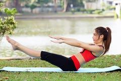 La jeune jolie femme faisant le yoga s'exerce en parc photographie stock