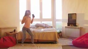 La jeune jolie femme heureuse dans des écouteurs seul dansant dans la chambre avec la grande fenêtre écoutent la musique sur le s banque de vidéos