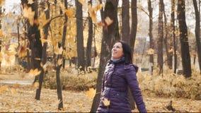 La jeune jolie femme heureuse de brune jette les feuilles d'automne en parc banque de vidéos