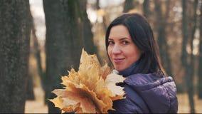 La jeune jolie femme heureuse de brune pose avec le bouquet des feuilles d'automne en parc clips vidéos