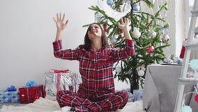 La jeune jolie femme heureuse jette des confettis près de l'arbre de Noël dans le studio décoré Mouvement lent 3840x2160 banque de vidéos