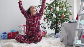 La jeune jolie femme heureuse jette des confettis près de l'arbre de Noël par la fenêtre Mouvement lent 3840x2160 banque de vidéos
