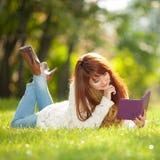 La jeune jolie femme a lu le livre électronique en parc Images stock