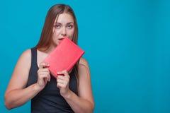 La jeune jolie femme mord un livre rouge se tenant dans des ses mains, images libres de droits