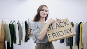 La jeune jolie femme pose avec un sac noir de vendredi dans une salle d'habillement banque de vidéos