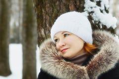 La jeune jolie femme s'est penchée contre l'arbre en parc d'hiver Photo stock