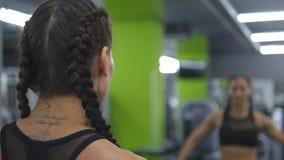La jeune jolie femme s'exerce dans le gymnase soulevant et abaissant des haltères devant le miroir Fille de forme physique de spo Images stock