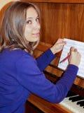 La jeune jolie fille avec les cheveux blonds situe près du piano, écrit les notes musicales et regarde l'appareil-photo Photo stock