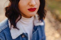 La jeune jolie fille avec les lèvres rouges et les cheveux courts dans un manteau de denim marche dans la ville d'automne image stock