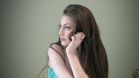 La jeune jolie fille de portrait avec de longs cheveux bruns corrige ses coiffures concept de pensée et de concentration clips vidéos