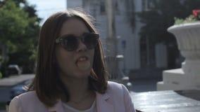 La jeune jolie fille mâche un chewing-gum, extérieur banque de vidéos