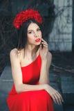 La jeune jolie fille pose avec des fleurs photos stock