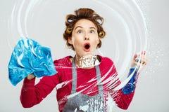 La jeune jolie fille stupéfaite lave des fenêtres avec la serviette bleue photographie stock