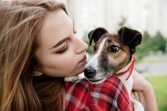 La jeune jolie fille tiennent son chien blanc d'isolement de vue arrière Fin vers le haut Images libres de droits