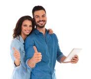 La jeune lecture occasionnelle de couples sur le comprimé et font le signe correct Image libre de droits