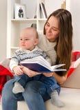La jeune mère affiche à l'enfant le livre Images libres de droits
