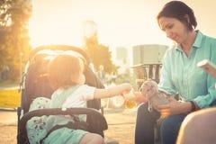 La jeune mère alimente à l'enfant la petite fille dans la voiture d'enfant photos stock
