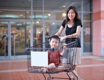La jeune mère asiatique et son enfant vont faire des emplettes Image stock