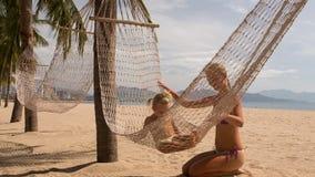 la jeune mère assied la petite fille pour balancer à travers des palmiers banque de vidéos