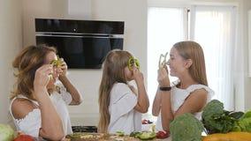 La jeune mère avec de belles deux filles prépare ensemble la cuisine de salade à la maison ils ` au sujet de jouer avec des tranc clips vidéos