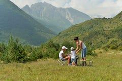 La jeune mère avec deux filles détendent en nature dans les montagnes photo libre de droits