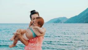 La jeune mère avec son petit bébé ont l'amusement sur une plage dans le jour d'été banque de vidéos