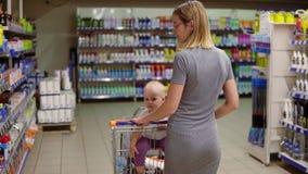 La jeune mère avec son petit bébé s'asseyant dans un chariot d'épicerie dans un supermarché marche en avant L'enfant regarde banque de vidéos