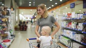 La jeune mère avec son petit bébé s'asseyant dans un chariot d'épicerie dans un supermarché pousse le chariot marchant en avant p banque de vidéos