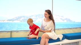 La jeune mère avec son petit fils est assise sur le bateau banque de vidéos