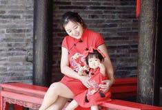 la jeune mère chinoise de famille heureuse a l'amusement avec le bébé dans le cheongsam traditionnel de la Chine Images stock