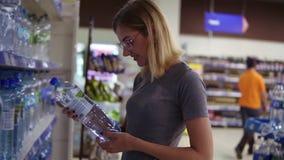 La jeune mère choisit une bouteille de l'eau dans le département de boissons dans le supermarché, alors que son petit bébé s'assi banque de vidéos
