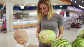 La jeune mère choisit une pastèque, le montrant à son petit enfant ce qui s'assied dans un chariot d'épicerie famille banque de vidéos