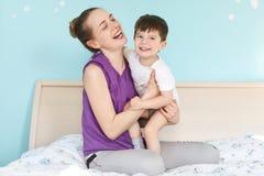 La jeune mère comblée et le fils sourient joyeux, ont l'amusement ensemble, se reposent sur le lit confortable dans la chambre à  photographie stock libre de droits