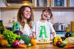 La jeune mère de cuisinier se tenant avec son petit fils dans le kitche Image libre de droits