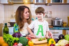 La jeune mère de cuisinier se tenant avec son petit fils dans le kitche Images libres de droits