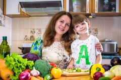 La jeune mère de cuisinier se tenant avec son petit fils dans le kitche Photographie stock libre de droits