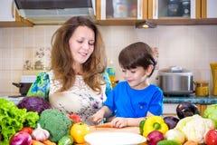 La jeune mère de cuisinier se tenant avec son petit fils dans le kitche Images stock