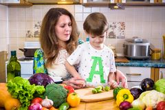 La jeune mère de cuisinier se tenant avec son petit fils dans le kitche Image stock