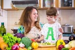 La jeune mère de cuisinier se tenant avec son petit fils dans le kitche Photographie stock